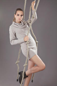 Young woman in jersey dress climbing rope against grey background, portrait