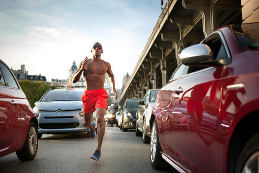 Athletic man running amidst traffic in European city, Bir-Hakeim Bridge in background, low angle