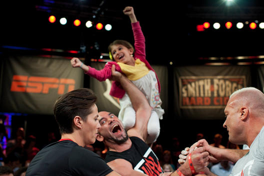 A girl jumps above the crowd and the winning competitor cheers at the arm wrestling competition in Las Vegas