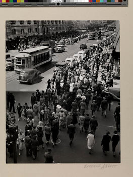 Crowd of people crossing a busy street.