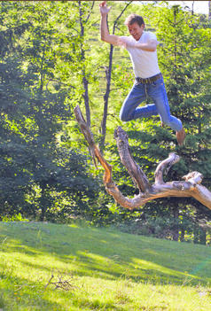 Man Jumping Off Of A Apple Tree Stump