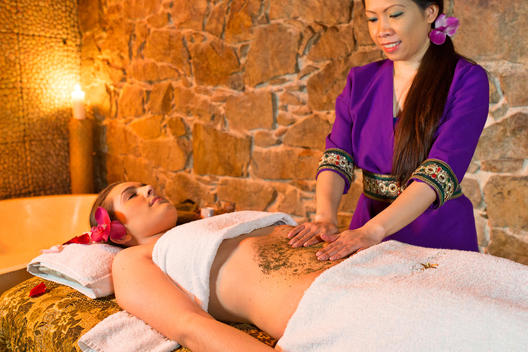Female Massage Therapist Giving Woman Herb Massage