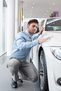 At the car dealer, Salesman cleaning car wing