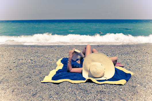Woman Reading On Beach, Calabria, Italy