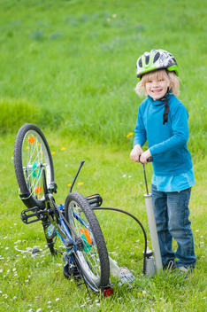 Little boy inflating bicycle tire on a meadow