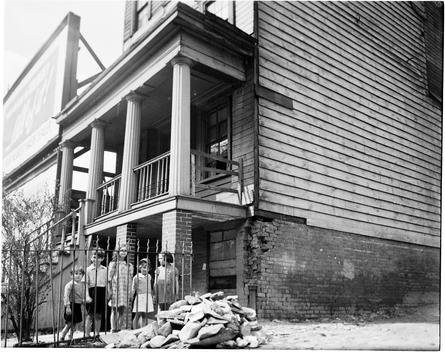 View Of Children Behind An Iron Fence And A Dilapidated House Behind Them.