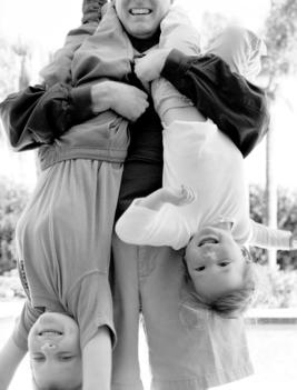 A Father Holds His Two Children Upside Down.
