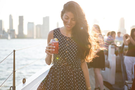 Woman enjoying a drink on crowded party boat
