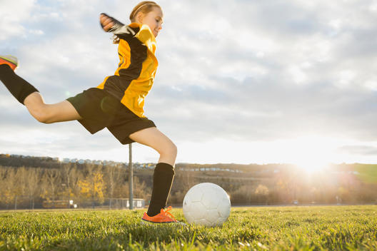 Girl kicking soccer ball on field