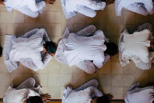 Followers of the Cao Dai religion pray in the Great Temple of Cao Dai. Tay Nihn, Vietnam