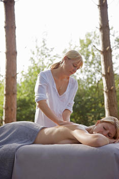 Massage therapist massaging woman back in a forest