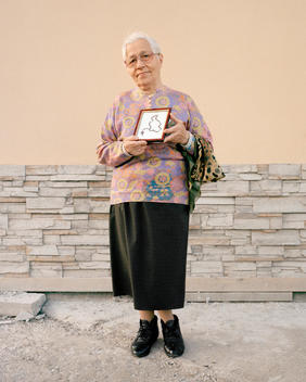 An Elderly Survivor Of The Soviet Gulags Holds A Framed Necklace Made From Breadcrumbs.