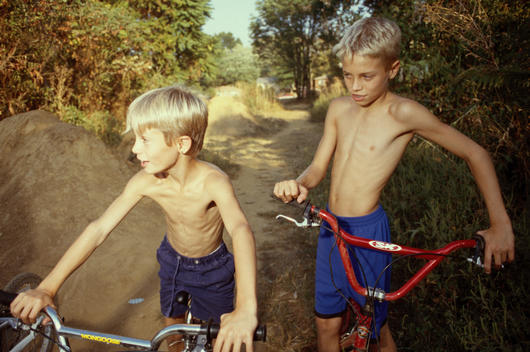 Two boys wearing no shirts set off for a BMX biking adventure, Louisville, Kentucky, USA.