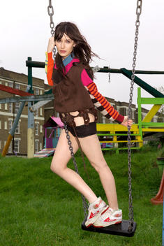 Young woman standing on swing in park.