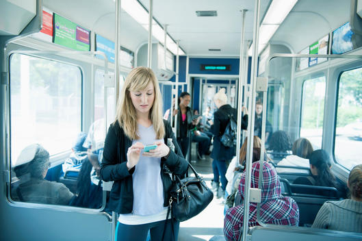 Caucasian woman using cell phone on train