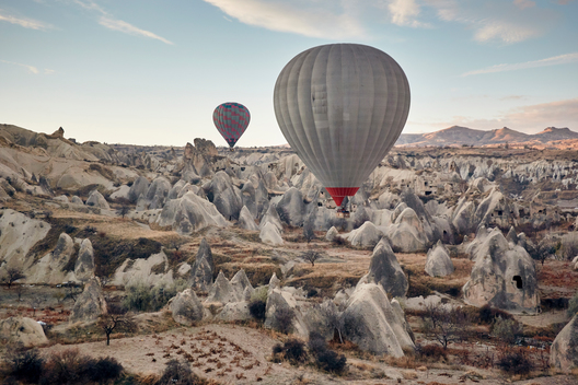 Soft dawn light on vast landscape of curious rock formations. Above them low to the ground hover two large hot air balloons.