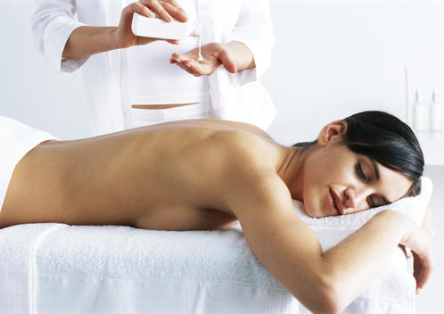Woman lying on stomach on massage table, woman pouring massage oil from bottle in background