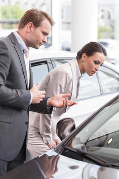 At the car dealer, Salesman showing new car to client
