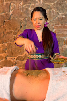 Female Massage Therapist Giving Herb Massage