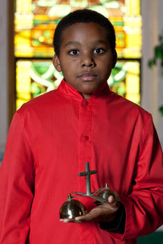 Portrait Of Young Altar Boy Of African-American Appearance In Catholic Church.