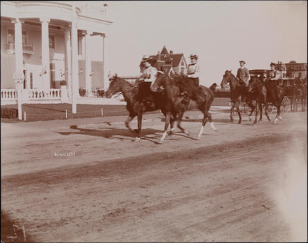 Men And Women Horseback Riding On Dirt Road In Front Of A Large Neo-Classical House.