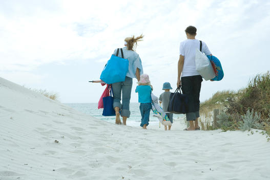 Family walking through dunes to beach