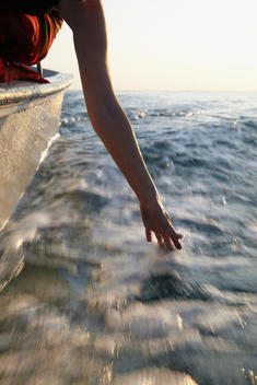 Senior Woman In Motorboat, Hand In Water