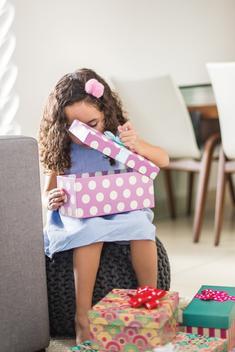 Happy child girl opening gift box
