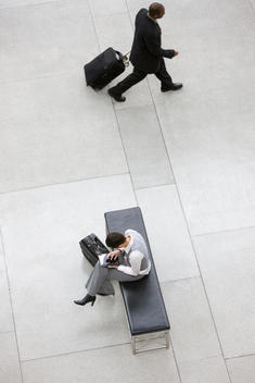 Business people with luggage in lobby