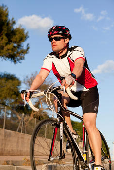 A Man Wearing A Full Bike Racing Outfit And He Is Cycling On The Road.