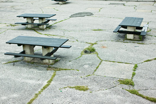 Empty Picnic Tables In Paved Courtyard