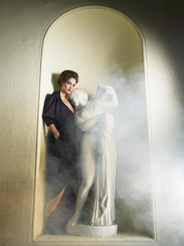 Fashion Story, Woman Standing In An Alcove Beside A Statue With Some Mist Flowing Past
