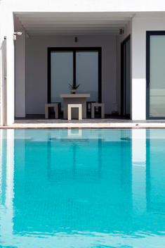 Minimalist architecture, a modern mansion reflected in the gentle ripples of an infinity pool