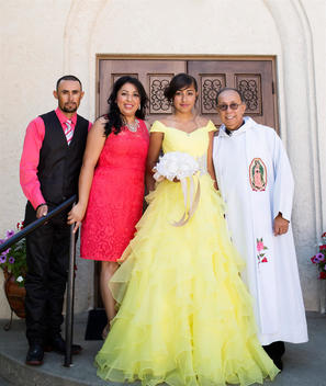 Hispanic family celebrating quinceanera with priest outside Catholic church