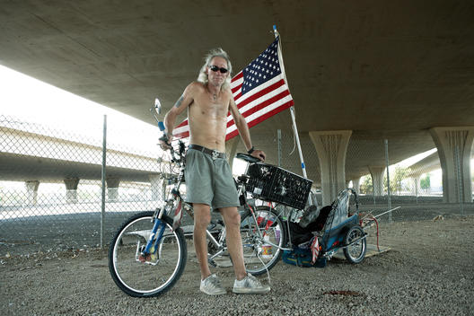 Homeless American veteran stands beside his bicycle under an overpass.