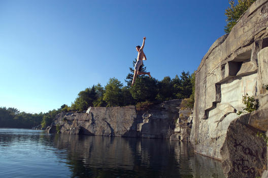 Young Man Jumping From A High Rock Into A Lake