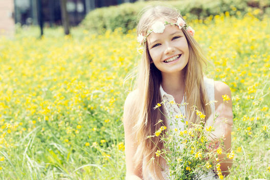 Portrait of a happy girl sitting on a flower meadow wearing flowers