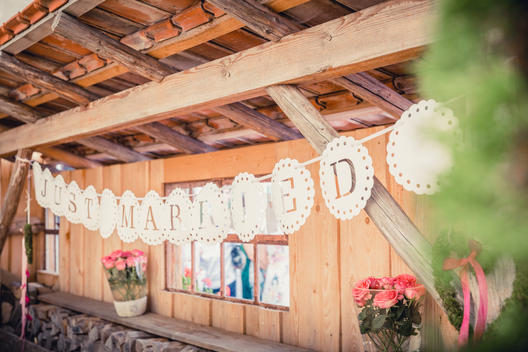 just married letters in lace flags, wooden background, wedding decoration with pink flowers