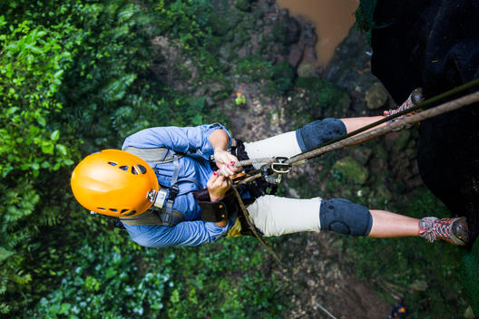 A woman rappels down a cliff while on an adventure in Puerto Rico, USA..