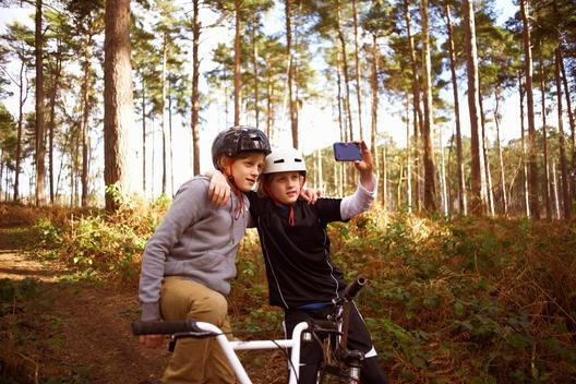 Twin brothers on BMX bikes taking self portrait
