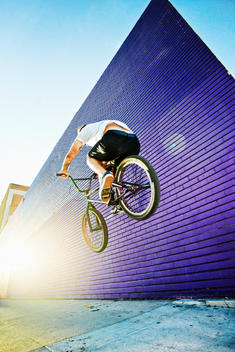 Caucasian man jumping on BMX bike