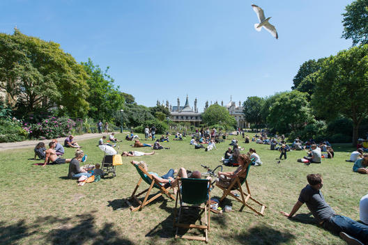 The public enjoying the sunshine while a seagull flies over the crowds in the gardens of Brighton Pavilion in Sussex