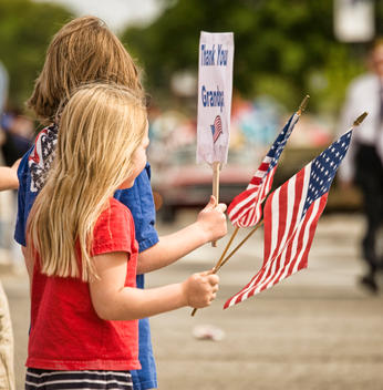 Young girls at Memorial Day parade holding up signs thanking their Grandpa for hi s service