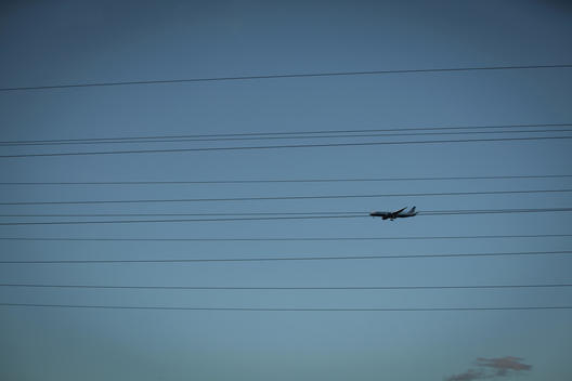 An Airplane going in for a landing at SFO that look as if it is suspended by High Voltage Power Lines