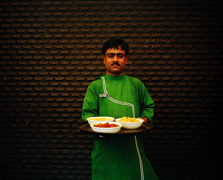 Waiter dressed in traditional clothes holding tray of dishes.