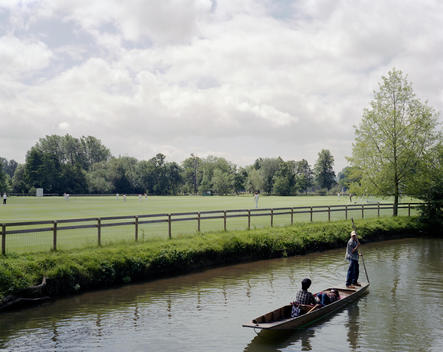 Tourists enjoy punting on the River Cam through Cambridge. In the distance a cricket match is underway on the green.