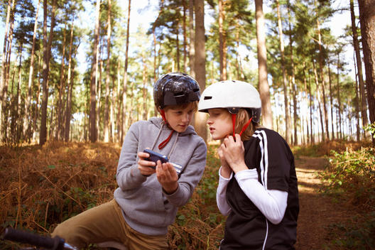 Twin brothers on BMX bikes in forest looking at smartphone