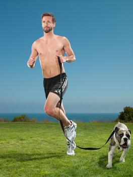 An athletic man is running with his dog beside him