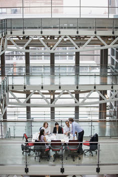 Business people meeting at conference table on atrium balcony