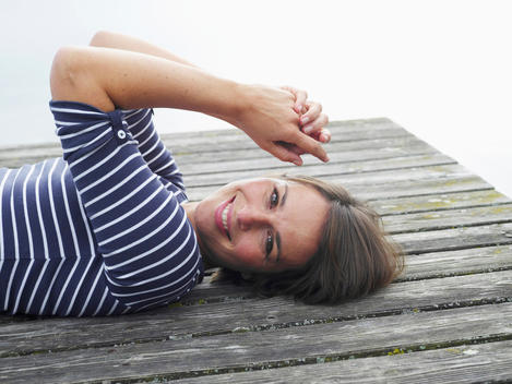 Germany, Munich, Mature woman lying on jetty beside lake, smiling, portrait
